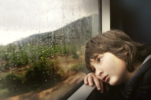 niño mirando por la ventana con cara triste